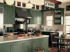 The deep green cabinets in this modern space create a beautiful, cozy island-shaped cottage kitchen.