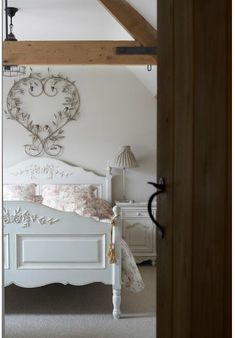 The old wood beams provide a geometric contrast to the curlicue heart and feminine carving on the bed. Very elegant - and restful!