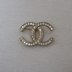 Vintage 70's CHANEL Rhinestone Brooch Pin A dazzling classic Chanel piece from the 1970's! Brooch is in excellent condition, and is a perfect addition to any wardrobe. Add some class in multiple ways with this versatile jewel. Place it on a purse, sweater, scarf or even a favorite hat! There are no markings on the back of the brooch so there is no way to tell if this is an authentic Chanel item. Brooch is made with excellent quality, heavy weight and well constructed and the price reflects…