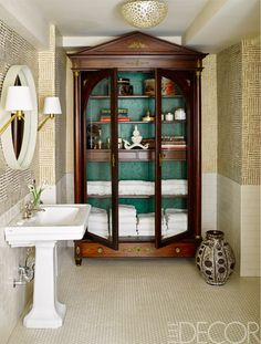 Cole & Son wallpaper lines the interior of an Empire cabinet in the master bath; the sink and fittings are by Waterworks, the mirror is by Made Goods, the sconces are by Aerin, and the wallpaper is by Sister Parrish Design. Decor Inspiration: Marisa Tomei's Manhattan Apartment of Her Dreams