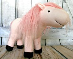 "My new Jellybean Pony Juliet is a pink foal with pink Tibetan lambskin mane and tail. She is made of high quality cotton interlock and is firmly stuffed with wool. Juliet has wool felt hooves and her face is handstitched. She will come home with her own custom foal day sheet.    This is her ""before"" picture.  I'm adding a unicorn horn and Pegasus wings!"