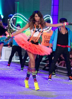 9. Victoria Secret Fashion show 2014: this look is a modern take on the Raver Style popular during the 80's and 90's and still seen by teens today, with its cut tee-shirt, suspenders, knee-high striped socks, glowing wings, tutu, and overall psychedelic and neon color scheme.