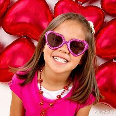 Get the best party photos of your little cupcakes with a photo booth backdrop of heart balloons. Give them fun wearable Valentines Day party favors to guarantee smiles and poses to melt hearts.