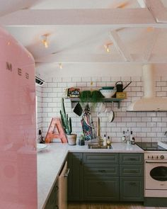 Modern kitchen with all the right details; millennial pink Smeg fridge, subway tile, marble counters, gray-green cabinets, open shelves and exposed wood beams.