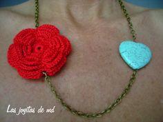 Collar corto realizado con cadena en color oro viejo. Roseta doble de croché en color rojo y turquesa con forma de corazón