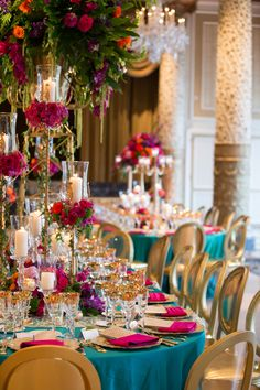 A breathtaking teal and gold themed table decor. Gorgeous pink rosettes with candlelight decorate the table with elegance.