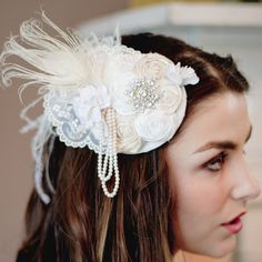 finest silks, feathers, pearls and rhinestones. This piece is made up in tones of ivory and white. The hand made rosettes are nestled amongst vintage white velvet petite flowers with strands of looped ivory pearls to embellish. This is topped with a eye-catching rhinestone accent. This fascinator