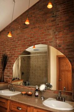 The bathroom on the first floor has a vaulted ceiling. The brick wall behind the mirror was the outside wall of the original brick home. A portion of it was badly damaged when the home caught on fire and it had to be rebuilt. The seam between the original portion and the rebuilt portion is visible above the mirror.