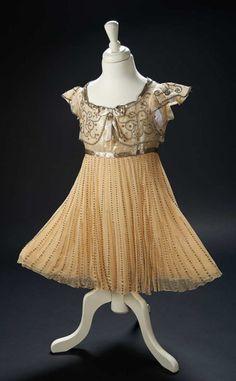 """Shirley Temple's """"I'll Build a Broadway for You"""" Dress from  1938 Film """"Little Miss Broadway"""" Of fine sheer organza, the skirt is trimmed with vertical tiers of rhinestones, while the high bodice is decorated with garlanded swirls of rhinestones and edged with silver metallic ribbons and bows. costume worn by Shirley Z"""