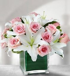 Fragrant white oriental lilies and pink roses are compactly arranged in a leaf lined glass cube.