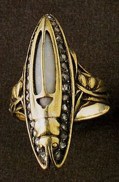 An Art Nouveau Beetle ring, by René Lalique, circa 1903. Gold, opal and diamonds. Signed LALIQUE. Gold ring with slim pointed beetle motif, the curved gold body set with an opal and edged with diamonds, the stylised antennae soaring backwards to form the outline of the insect. Source: The Jewellery of René Lalique, by Vivienne Becker. #Lalique #ArtNouveau #ring