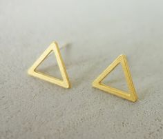 A chic geometric earings designed as two small hollow triangles. The unique element connects to a sterling silver ear rod. Made of high quality gold