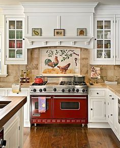 Country French at it s best! The red stove makes this the heart of the home. I love the tile mural, the cabinets, all of it! Very inviting- might even encourage me to cook!