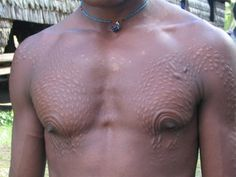 Sepik river rites of passage where males would have their skin cut with razors to form decorative scars resembling the sacred crocodile spirit, as part of turning young boys into men