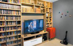 """Na sala de jogos pintada de cinza (cor Nanquim, ref. E161, da Suvinil), a marcenaria organizou as paixões do marido: de um lado, acomoda os mais de 500 DVDs e, do outro, expõe bonecos de filmes e games. """"O André adorou o frigobar com jeito cinquentinha. E o ambiente ganhou ar retrô"""", diz Gabriela. Estante de DVDs. De MDP (2,95 x 0,25 x 2,49 m), inclui rack (1,51 x 0,45 x 0,60 m)."""