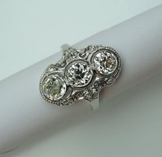 Platinum and diamond ring, bezel set with three round diamonds (2 European-cuts and 1 mine-cut). clarity I-1 and color J-K. Ring is also set with six small round diamonds (2 European-cuts and 4 single-cuts).  All nine diamonds have a total weight of 2.30-carats. The setting is has a swirly scroll motif with milgrain tooling. Edwardian or Edwardian style.