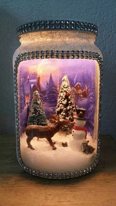 "Scene inside a jar.  Use frosted paint or glue and crystal glitter to cover all but the ""window"" of your container.  Add bits inside and trim outside as you like.  You could put a clear candle dish on top (make sure it sits securely!)  and a lit candle will cast light into the jar.  A craft for any season or scene!"