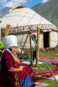 Kyrgyz woman on her mobile phone while weaving at the World Nomad Games in Kyrgyzstan.