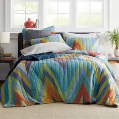 Patchwork quilt with supersized chevrons zigzagging across in hues of orange, gold, periwinkle, green, and blue. Shop handmade quilts at The Company Store. The Company Store Bedding Shop, Quilt Bedding, Whole Cloth Quilts, Home Decor Sale, The Company Store, Linen Bedroom, Twin Quilt, Quilted Bedspreads, Queen Quilt