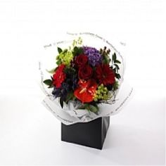 An expertly hand tied aqua packed bouquet of beautiful red roses, green anastasia, kermit santini, red gerbera, purple hydrangea, purple trachellium, hypericum berries, red anthurium and blue thistle, presented in exclusive Bumblebeez wrap and a black gift bag.