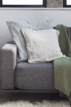 Modern hygge style in soft shades of grey = a beautiful Scandinavian style living room with cosy sheepskin and soft green throw to bring the look up to date.