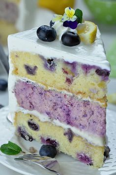 A decadent blueberry cheesecake kissed by lemon hiding inside a layer cake. Perfect summer cake. #lemon #blueberry #cheesecake #cake