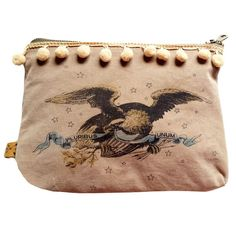 "E Pluribus Unum Cosmetic Bags by All Souls Mercantile. A Bald Eagle holds a ribbon saying ""E Pluribus Unum"" in his talons. Creme pom poms. Hand crafted from recycled military surplus. Individually hand airbrushed. 9"" x 6 1/2"". $35"