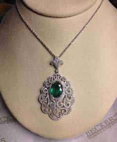 Antique-style scrollwork emerald pendant with diamonds in 14k white gold. Get it now at Becker's!