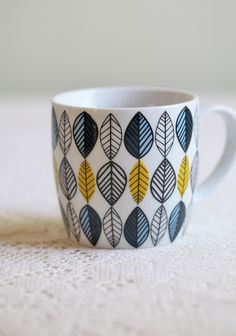 Modly Leaf Mug 12.99 at shopruche.com. Have your tea or coffee with this ceramic mug with a modern leaf print in shades of blue, white, and yellow. Dishwasher and microwave safe.  Approx. 3.5