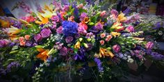 Vibrant casket pall in pinks, lavenders, purples and orange lilies. Funeral. Floral design by Steven McLellan, Garden Delights Florist, Franklin, TN 615-599-9950