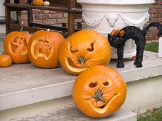 22 Traditional Pumpkin Carving Ideas: Dress up your porch by letting everyone in the family carve their own pumpkin. This set of jack-o'-lanterns evokes spooky elements of Halloween, except for the smiling, stalk-nosed pumpkin in front. From DIYnetwork.com