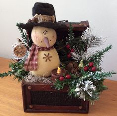 Vintage chest featuring a sweet vintage snowman wearing a stiffened felt top hat.....embellished with pine, frosted Ming, rusty jingle bells, lacquered berries, a grungy hang tag and a wax dipped, battery operated tea lite.