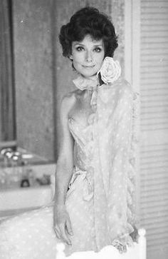 In March 1976, Audrey Hepburn Dotti photographed by Elisabetta Catalano at her apartment in Rome in the Parioli area. Audrey was wearing a Valentino evening gown (strapless, of yellow chiffon with white polka dots, a rose of starched satin on the neck holding a long scarf in the same tissue of the gown and ornamented with small ruffles, a ribbon at the waist also in the same tissue, from his couture collection for the Autumn/Winter 1972/73).
