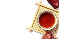 Une tasse de thé noir avec les dates rouges Photo libre de droits