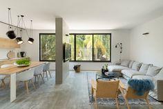 הצבעים שנבחרו לדירה - אפור, שחור, לבן ועץ - חוזרים מרמת המעטפת ועד לרהיטים ולגופי התאורה. נוף העצים מעשיר את מראה הסלון (צילום: גדעון לוין)