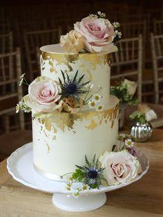 Smooth buttercream wedding cake with edible gold gilding.