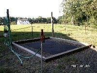 Simple wash stall with railroad ties, gravel base, and a rubber mat with posts set in concrete for cross ties. Can set two side-by-side with three posts.