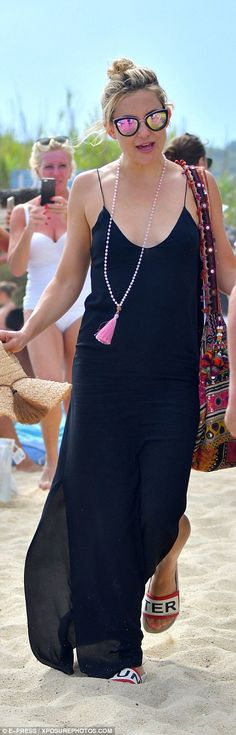 Classy: Kate added some more colour to her simple summer dress with a quirky mirrored carp...