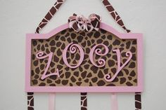 Pink and Giraffe Print Bow Holder. This custom made bow holder is adorable for little girls of any age! Hand painted with high quality acrylic paints. The name is done in wood letters so it gives a little 3D accent! A handmade bow is attached to the top. We can customize this how ever you like. Send us a picture or a link to your little girls bedding and we can paint it to match.