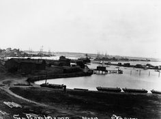 (late 1800s)* - Early view of San Pedro Harbor. Several ships can be seen anchored in the harbor. Train cars sit my a small wharf in the center of the photo.