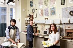 """Virginia Tupker, """"French Press: Exquisite Handmade Wallpapers From Parisian Studio Antoinette Poisson,"""" Architectural Digest (June 2014): 52. Brightly colored and boldly patterned, the handprinted papers made by the French team are as enchanting as the 18th-century examples that inspired them. Image (left-right): Vincent Farelly, Jean-Baptiste Martin, and Julie Stordiau of the studio Antoinette Poisson. Photo by Miguel Flores-Vianna."""
