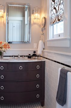 Gorgeous chic bathroom design with espresso bathroom cabinet vanity washstand, marble counter tops, polished nickel ring pulls hardware, beveled mirror, subway tiles backsplash,gray walls paint color, modern glass sconces and graphic blue & blacl roman shade.