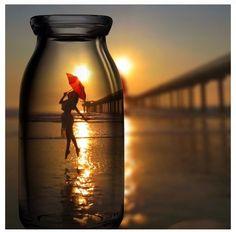Fotografia original, feta a una platja, on es superposa un envàs de vidre i al fons una dona amb un paraigues vermell , creant l'efecte que la dona es troba dintre de l'envàs.