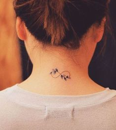 This delicate and feminine tattoo is of an infinity symbol, with purple flowers displayed in the lines. It fits the neck/top of the back perfectly but this would also look nice placed on other areas of the body. #tattoofriday #tattoos #tattooart #tattoodesign #tattooidea