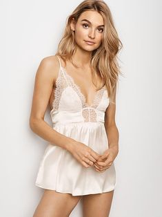 53921adea26 Simply irresistible  this plunge-front babydoll in smooth satin kissed with  Chantilly lace.