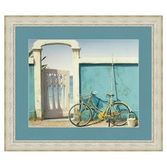 Depicting a bicycle leaning against a seaside wall, this American-made art print offers coastal appeal for your decor.  Product: