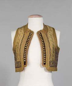 The layers of embellishment on this Albanian vest (4th quarter 19th century) include gold braid, gold cord in an intricate foliate pattern; and gold spangles. The lively patterned ikat lining adds to its festive appeal.