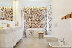 Biała łazienka przestronna i elegancka. Efektownie wygląda dekoracja ściany za wanną, wykonana z plastrów drewna.