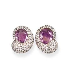 A PAIR OF AMETHYST AND DIAMOND EAR CLIPS. Each oval amethyst within a pavé-set diamond scroll border, mounted in 18k blackened and yellow gold, 2.4 cm long, with cream pouch. Stamped MdV for Michele della Valle.