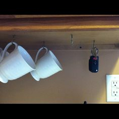 Use screw hooks to hang mugs and keys under the cabinet.